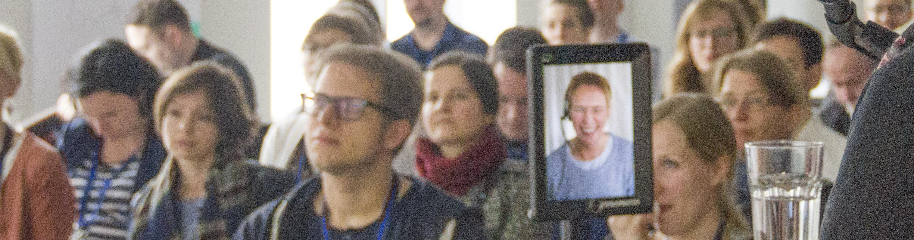 Telepräsentroboter sitzt im Publikum.